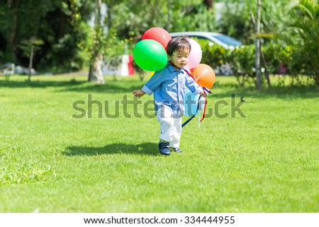 Little boy holding balloon and playing at park