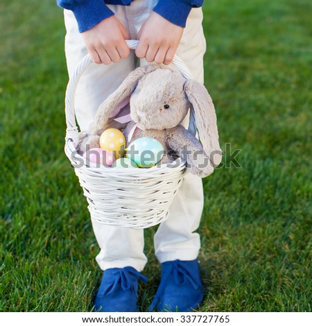 little boy holding basket with colorful easter eggs and bunny in the park enjoying spring time, no face visible - stock photo