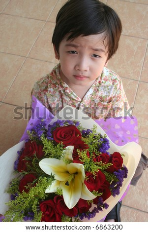Little boy holding bouquet of red roses and lily - stock photo