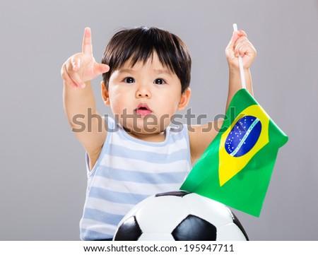 Little boy holding Brazil flag and soccer ball - stock photo