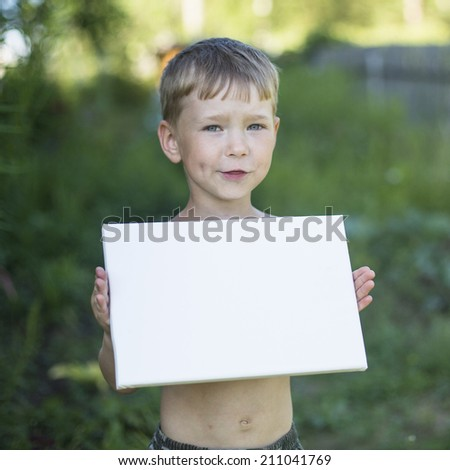 Little boy holding clean white sheet paper, outdoors (banner for your message) - stock photo