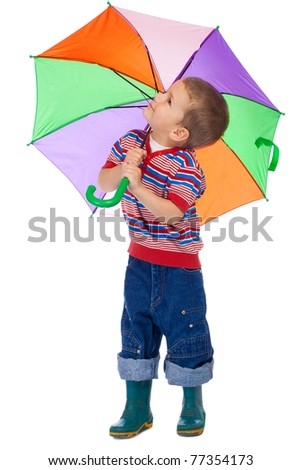 Little boy holding colored umbrella and looking to sky