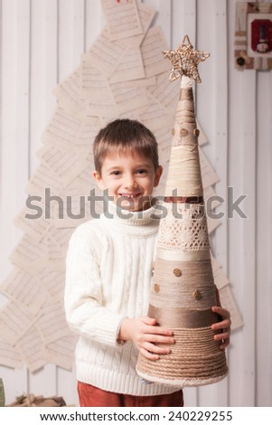 Little boy holding decorated Christmas tree in Christmas interior at home - stock photo
