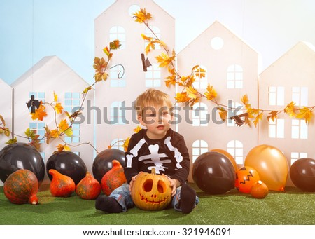Little Boy Holding Halloween Pumpkin Near Little Houses On Blue Background - stock photo