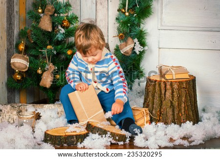 Little boy holding his christmas present - stock photo