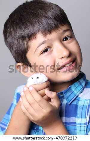 Little boy holding his hamster pet