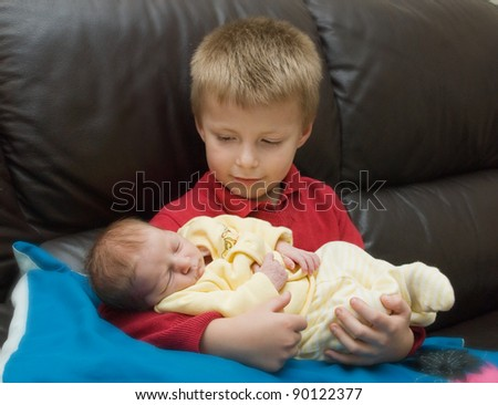 Little boy holding his newborn sibling - stock photo