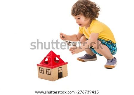 Little boy holding keys  to open  wooden house toy isolated on white background