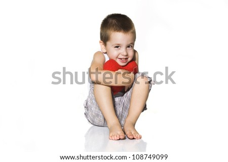 little boy holding red heart - stock photo
