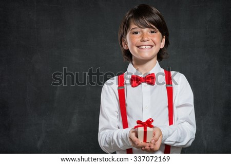Little boy holding small gift box in hand. Child smiling and looking at camera isolated on blackboard. Portrait of cute gentleman holding a wrapped gift box in hand for valentine's day. - stock photo
