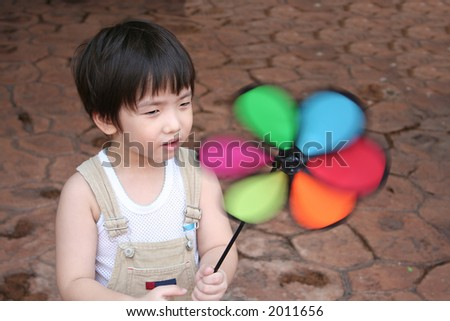 Little boy holding spinning windmill on a windy day - stock photo