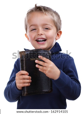 Little boy holding the bible and smiling isolated on white