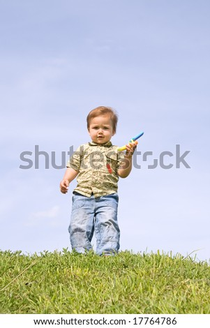 Little boy holding toy cellphone - stock photo