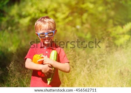 little boy holding vegetables in summer garden - stock photo