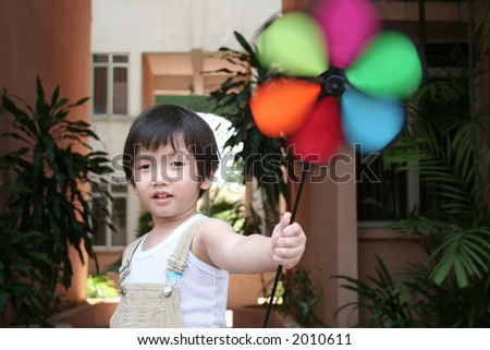 Little boy holding windmill on a windy day - stock photo