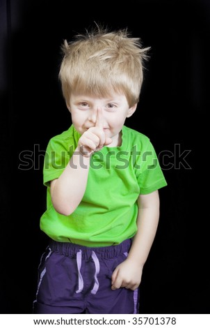 Little boy holds his finger to his lips. - stock photo