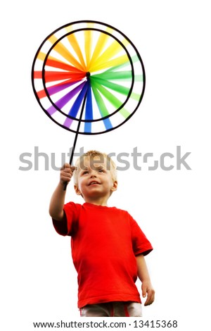 Little boy holds up a toy windmill - stock photo