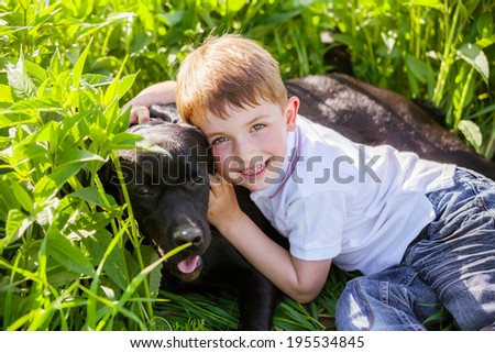 Little boy hugging a big dog in an outdoor setting - stock photo