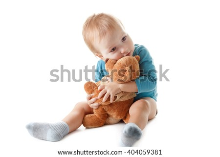 Little boy hugging a teddy bear isolated on a white background