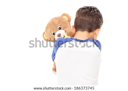 Little boy hugging a teddy bear isolated on white background - stock photo