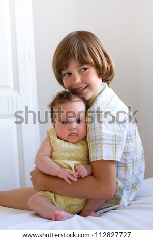 Little boy hugging and enjoying his newborn sister