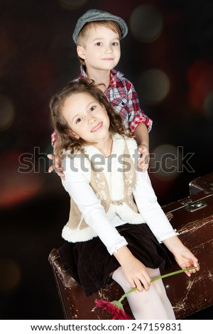 Little boy hugging beautiful smiling little girl with red flower. Valentine day - stock photo