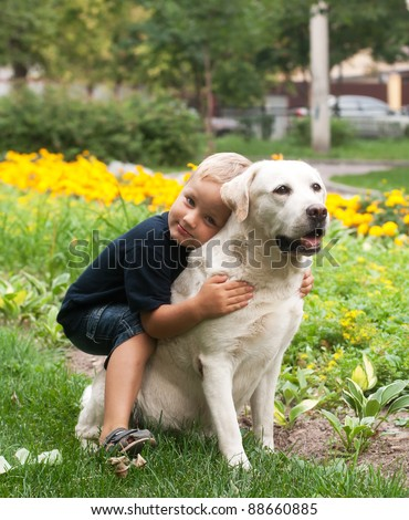 Little boy hugging his yellow labrador retriever