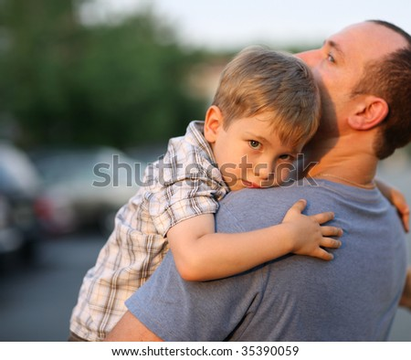 Little boy hugging hugging father around shoulders - stock photo