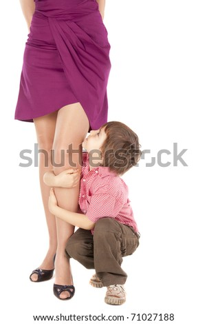 Little boy hugging the leg of his young mum - stock photo