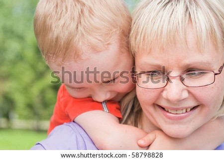 little boy hugs his mother's neck with all his strength