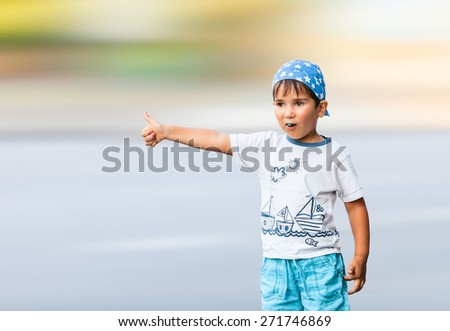 Little boy in a bandana vote on city road - stock photo
