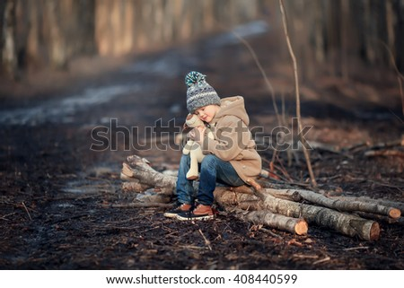 little boy in a beige coat, blue jeans and sneakers sitting on a branch in the park and hugging a toy dog - stock photo