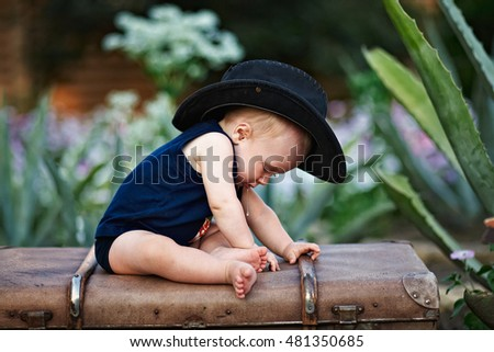 Little boy in a black hat sitting on a vintage suitcase in the garden