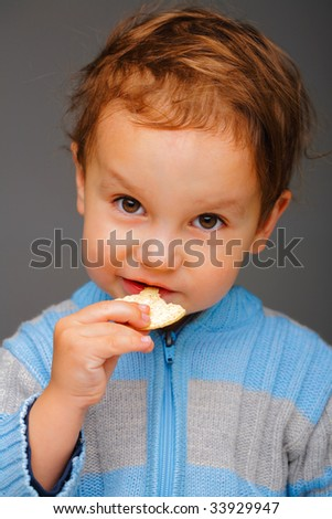 Little boy in a blue sweater eating a cookie, in studio