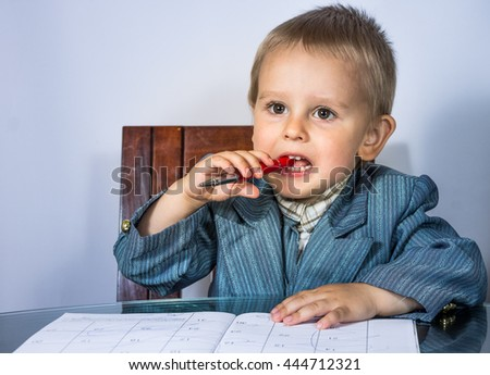 Little boy in a business suit talking on the financial issues at the round glass table