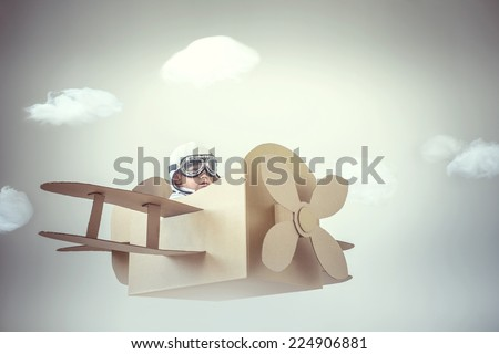 Little boy in a cardboard airplane - stock photo