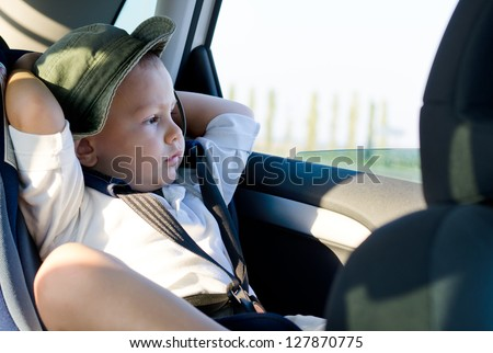 Little boy in a child safety seat sitting patiently in the back of a car with his hands behind his head staring out of the window - stock photo