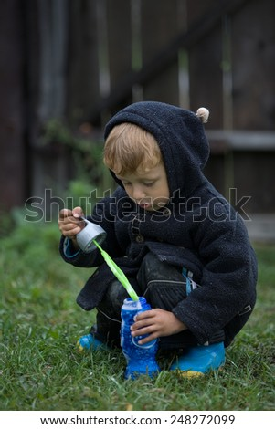 little boy in a dark blue jacket blows soap bubbles in the autumn - stock photo