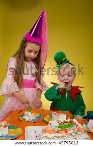 little boy in a green suit sitting at a table eating cake - stock photo