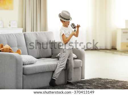 Little boy in a hat singing into the microphone at home - stock photo