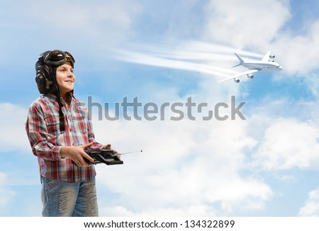little boy in a helmet pilot keeps remote control, in the background plane and sky - stock photo