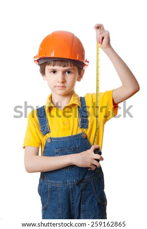 Little boy in a helmet plays in the builder, isolated on white background