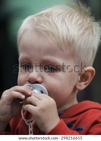 Little boy in a red jacket  with a  with a pacifier - stock photo