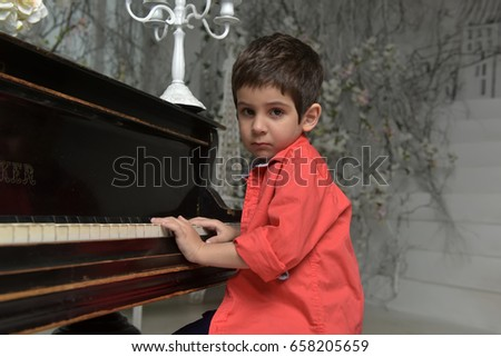 Little boy in a red shirt near the piano