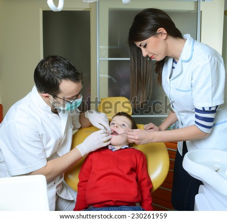 little boy in a red sweater went to the dentist in the dental chair sits next to a doctor to do the dentist to see if his teeth were okay/little boy in a red sweater went to the dentist