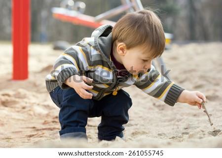 little boy in a sandbox / little boy - stock photo