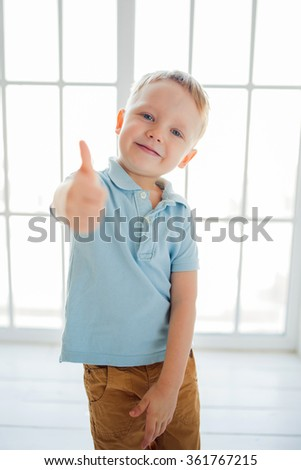Little boy in a shirt shirt making thumbs up and smile - stock photo