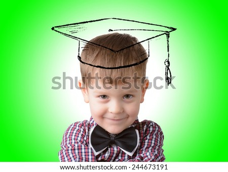 little boy in a square academic cap on a green background - stock photo