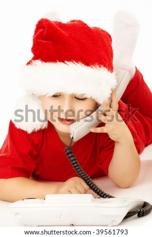 Little boy in a suit of santa lies and speaks on the phone, isolated - stock photo