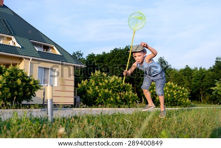Little boy in a sunhat standing poised to catch an insect with his net in the grass outside his house - stock photo